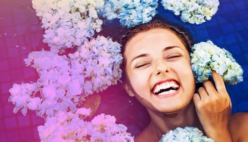 Beautiful image of stock photo of laughing woman in water with floating flowers