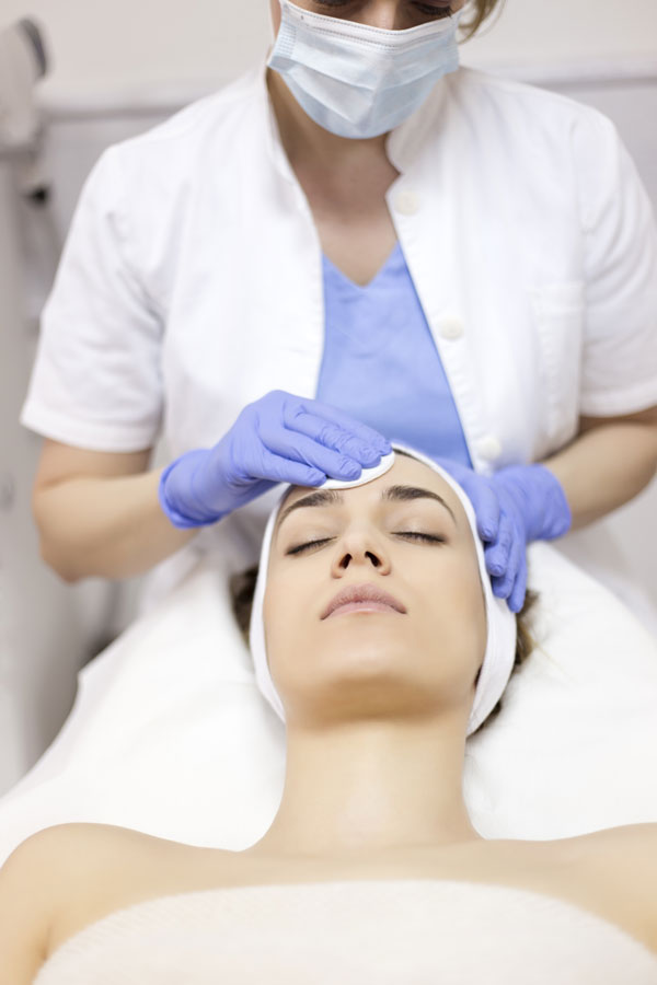 stock image of aesthetician preparing skin